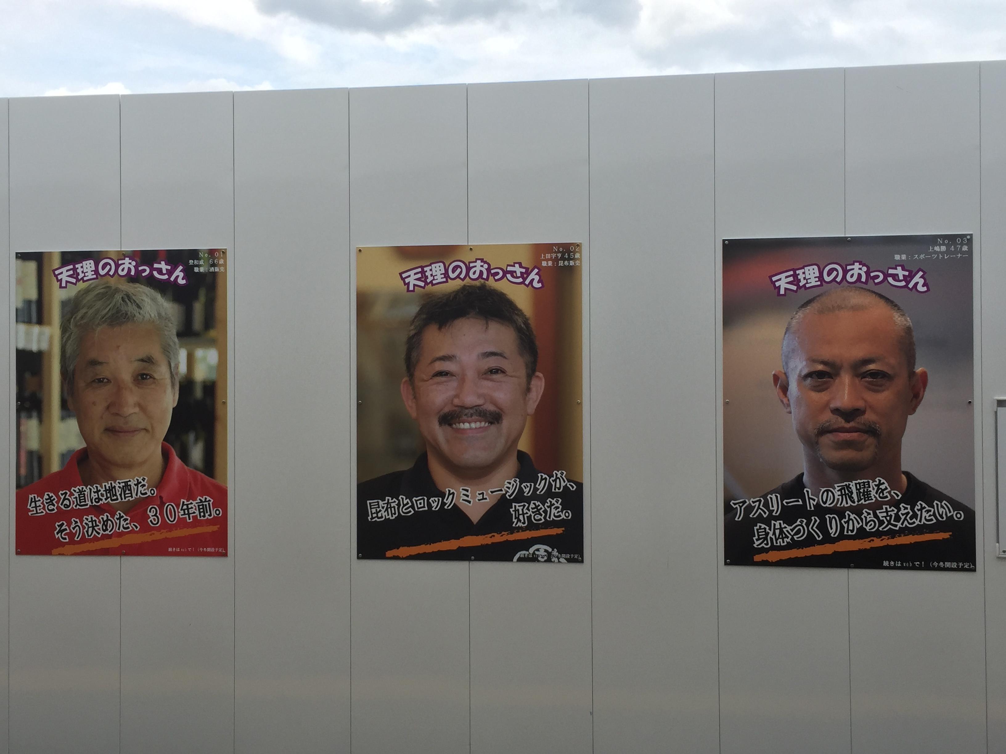 天理駅前の工事現場の仮囲いの装飾がオモシロイ!天理のおっさんの顔写真が!